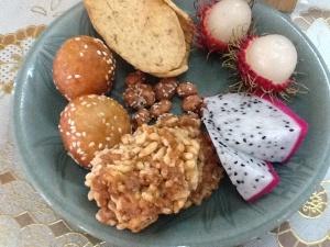 Buñuelos, pan de gamba, lichis,  una especie de torta de arroz y en el centro cacahuetes garrapiñados.