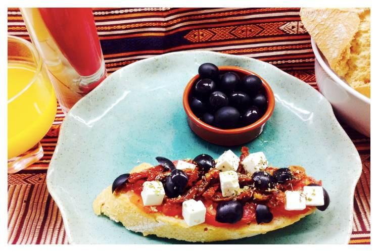 Tosta de queso feta con aceitunas negras, tomates y orégano